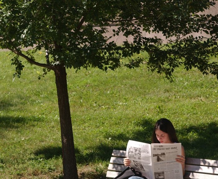 Photo: A student reading a newspaper on an outdoor bench